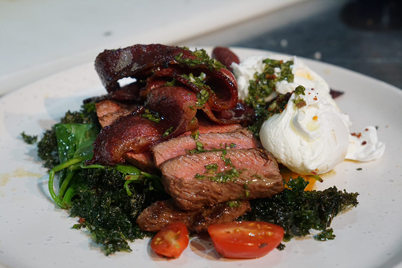 The prepared Angus recipe of BBQ True Aussie Angus Flat Iron, sautéed greens, Basturma salted Poached Egg, Crispy Beef Bacon, Chimmi Churri,with blistered heirloom tomatoes